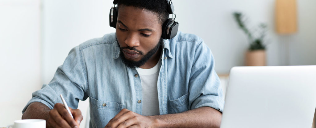 Man with headphones studying by a laptop